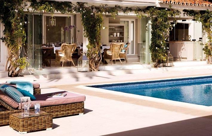 Внутренний двор с бассейном и плетеными шезлонгами