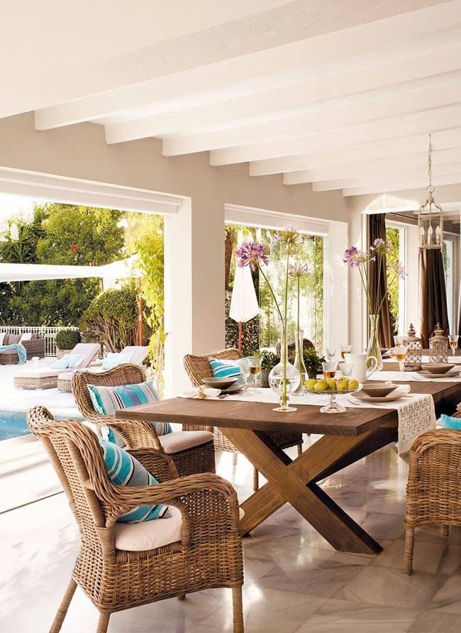 Крытая терраса с обеденным столом и удобными креслами фото