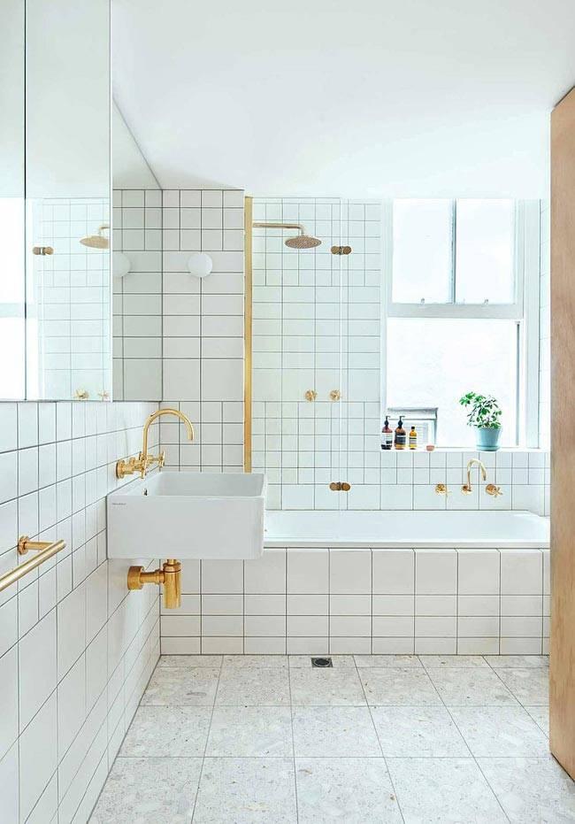 Минималистичный белый интерьер ванной с золотой фурнитурой