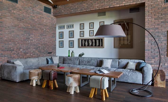сочетание белой и кирпичной стены возле большого дивана