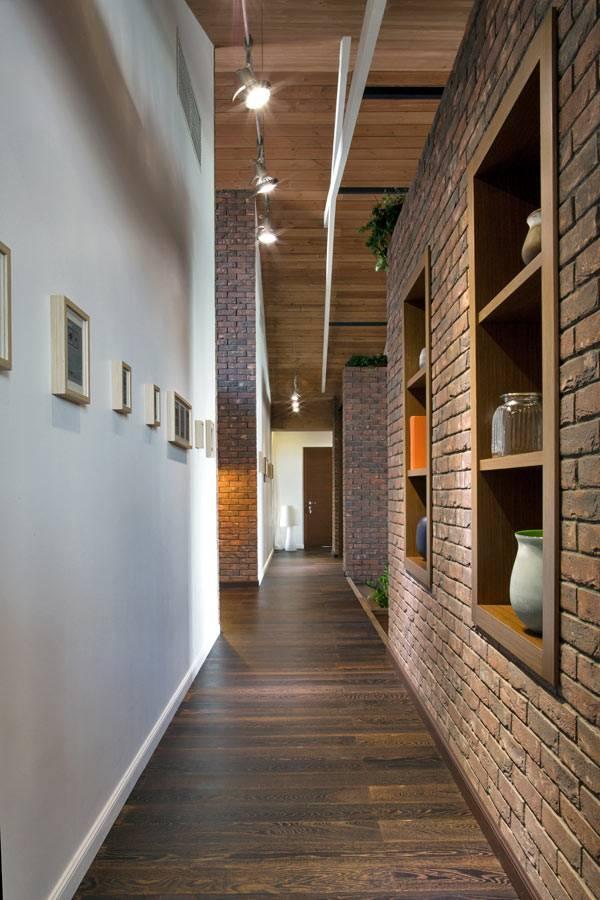 кирпичная стена с нишами для хранения в прихожей дома