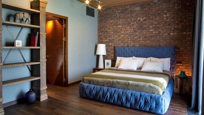 Кирпичная стена и синяя кровать в дизайне современной спальни