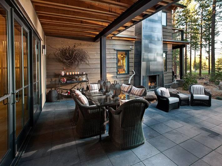 открытая терраса с плетеной мебелью и видом на лес