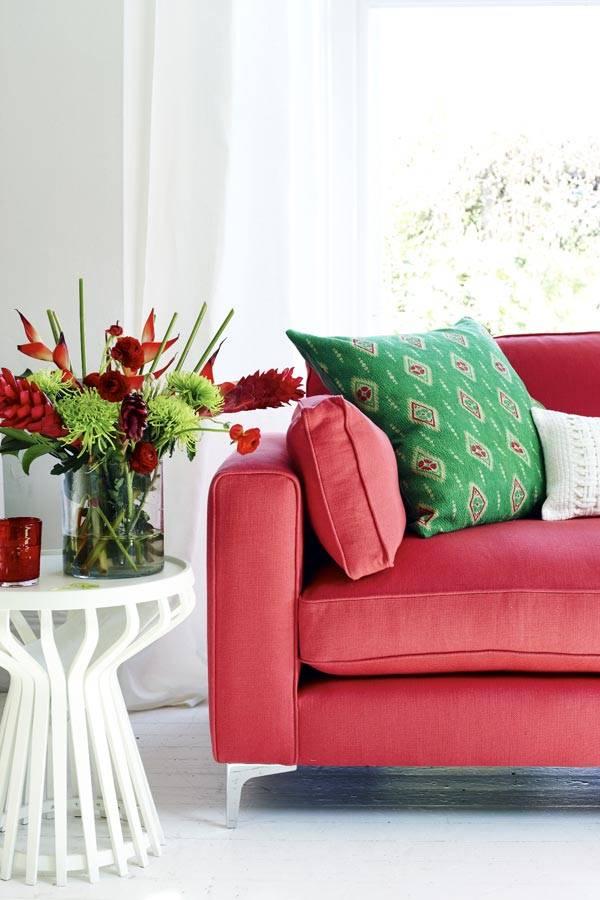 ярко-красный диван и зеленая подушка выделяется в белой комнате