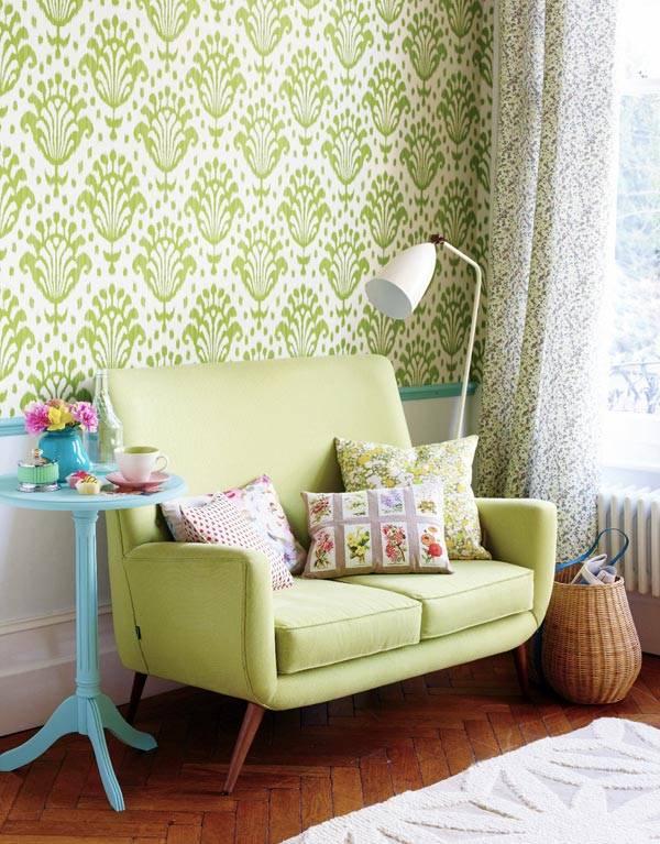 Зеленый диван на фоне зеленой стены в интерьере комнаты
