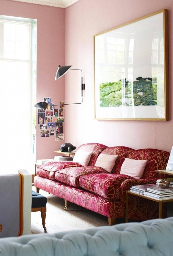 Красный диван на фоне розовой стены фото