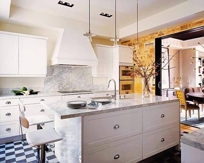 Белый интерьер кухни с рабочим островом в доме в Мадриде