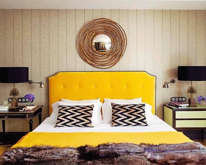 Кровать с желтым изголовьем и круглым зеркалом в спальне