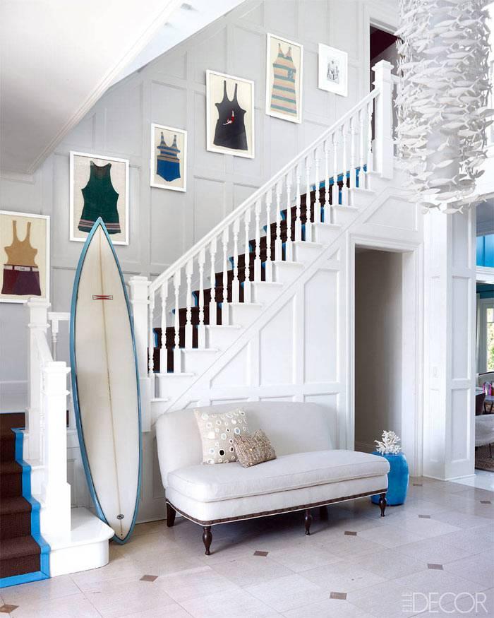 просторный холл белого цвета и доска для серфинга как декор