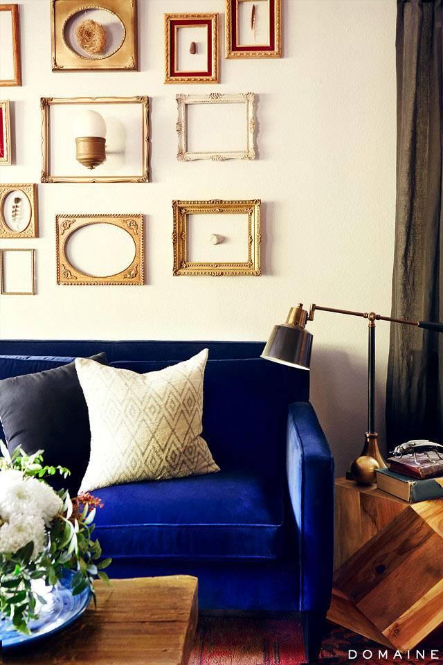 Красивый декор стены пустными рамами над диваном