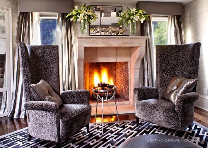 зона отдыха с двумя креслами возле камина с живым огнем