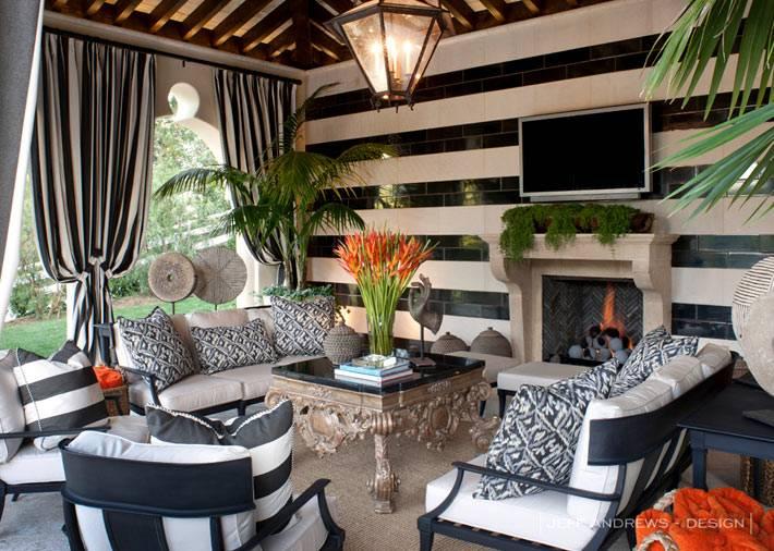 дизайн крытой террасы с мягкой мебелью и камином