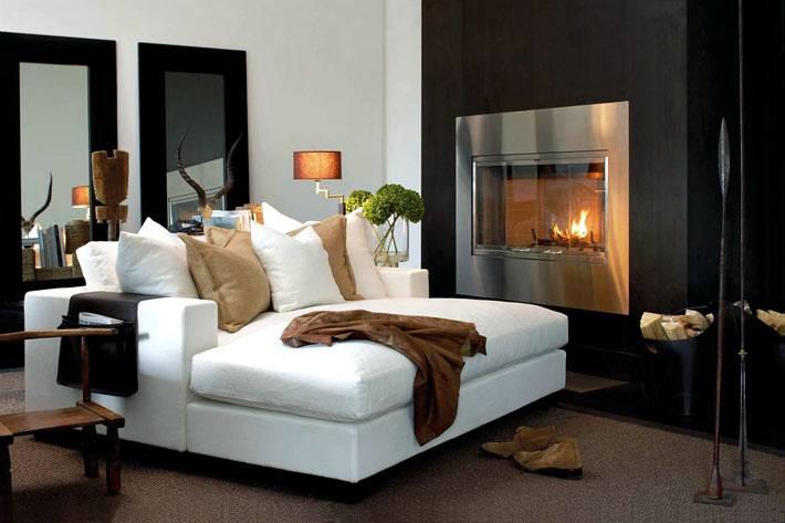 закрытый электрический камин черного цвета возле белого дивана