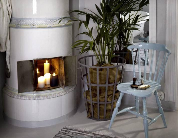 Камин-печь со свечами в интерьере квартиры