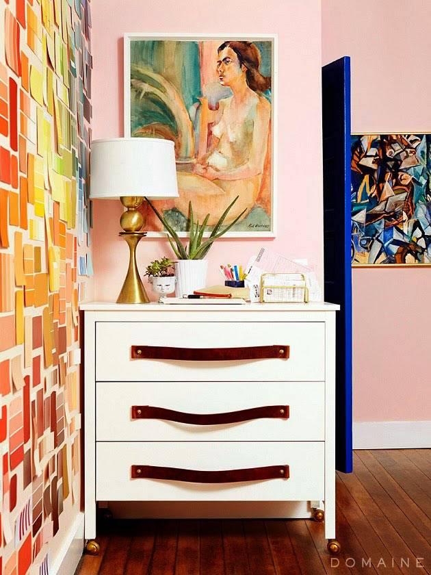 белый комод с кожаными ручками возле розовой стены