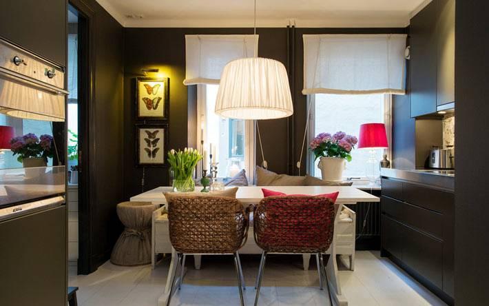 красивый интерьер кухни в темных тонах и белым столом