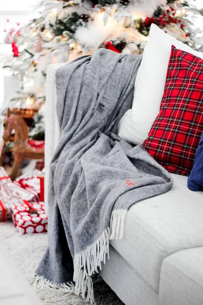 Уютный новогодний декор дома с яркими подушками и теплым пледом
