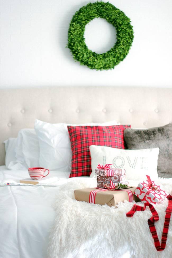 новогодний венок из зелёных листьев в спальне над кроватью
