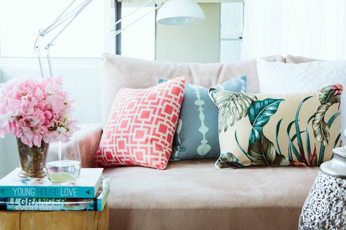 разноцветные диванные пожушки и цветы в украшении дома