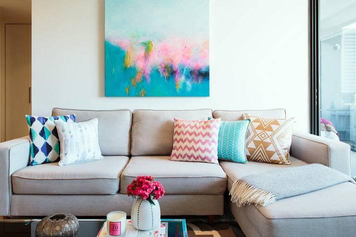 угловой диван светло-серого цвета и яркая акварельная картина