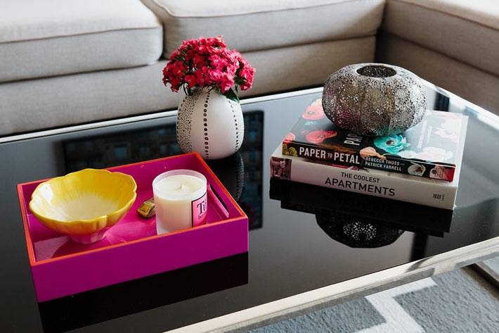 розовый поднос на зеркальном черном столе в гостиной
