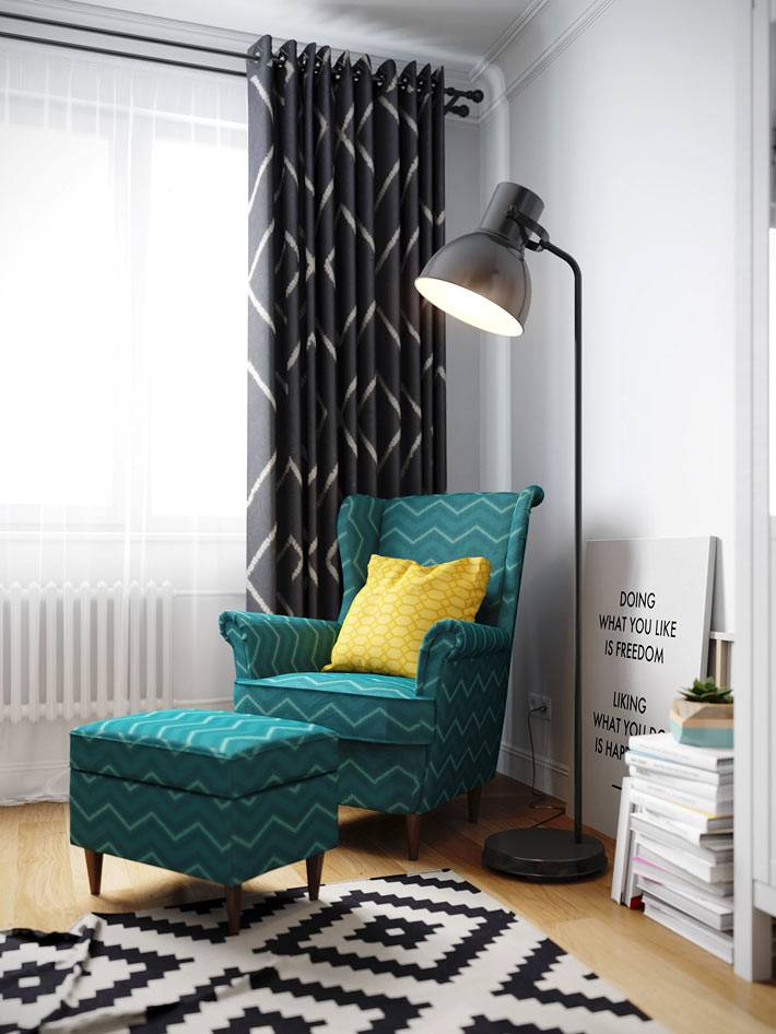 зеленое кресло с подножкой и черный торшер в комнате