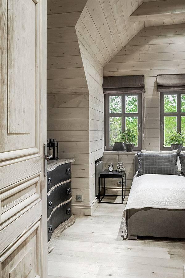 деревянный интерьер спальной комнаты под крышей дома фото