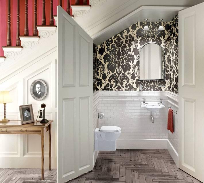 Красивый интерьер дополнительной туалетной комнаты под ступенями