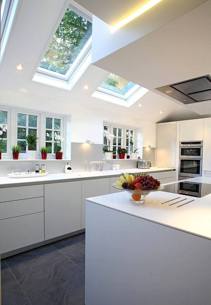 современная кухня белого цвета с мансардным окном