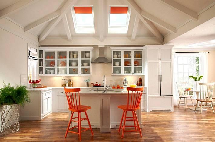 два мансардных окна с оранжевыми шторами на кухне