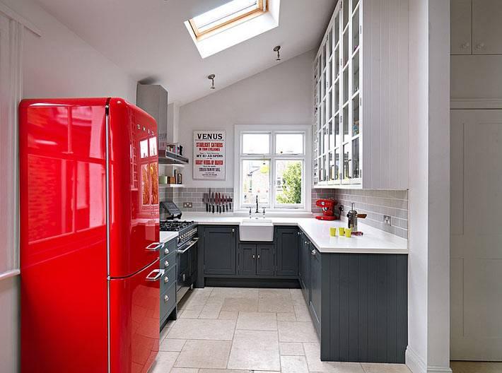 компактная кухня с красным холодильником и мансардным окном