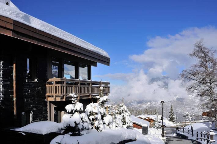 красивое шале с видом на зимние заснеженные альпы