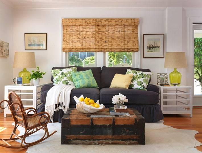старинный сундук в центре гостиной с плетеной мебелью
