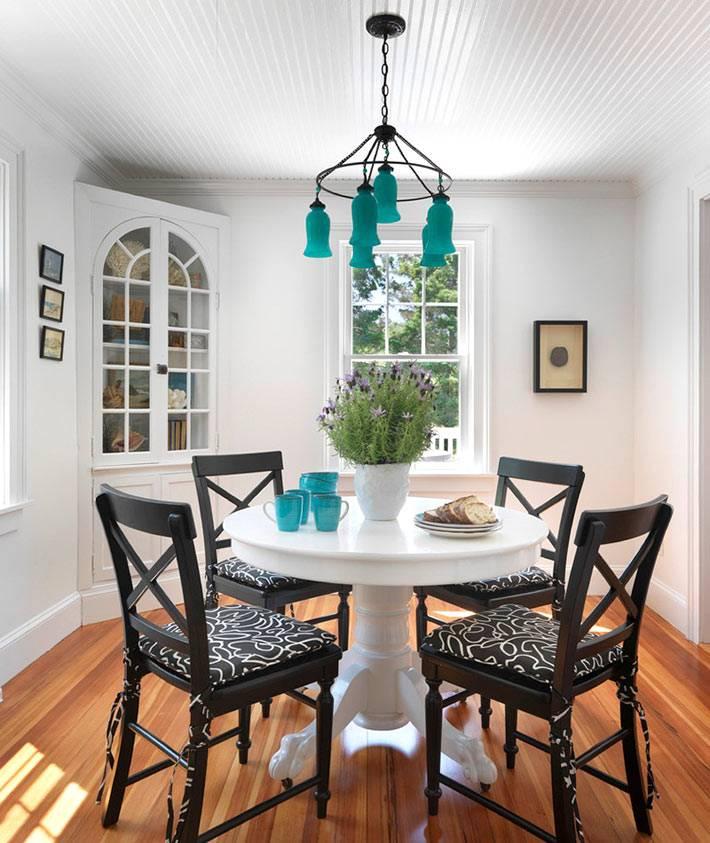 интерьер столовой с черными стульями и бирюзовой люстрой