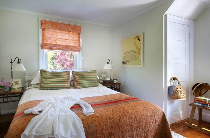 оранжевая римская штора на окне в спальне