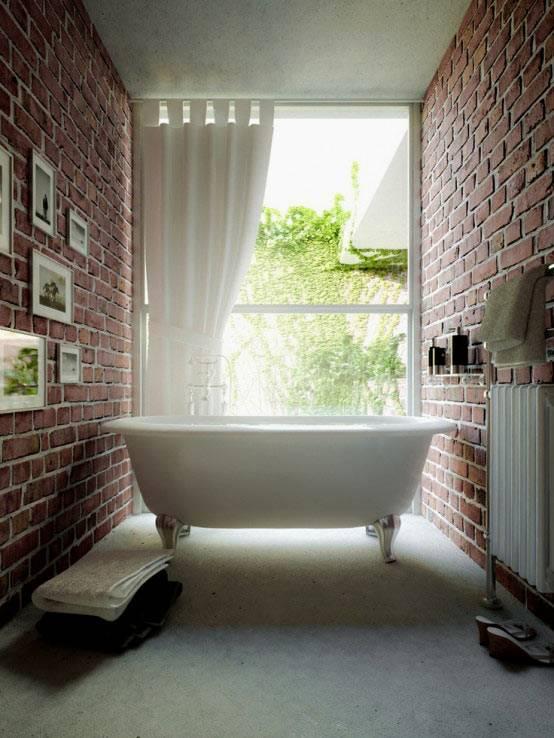 Интерьер ванной комнаты с большим окном и кирпичными стенами