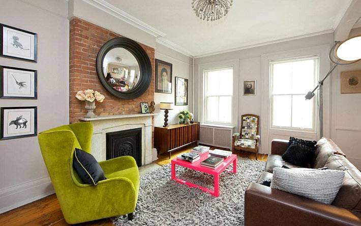 камин и зелёное кресло в интерьере гостиной комнаты