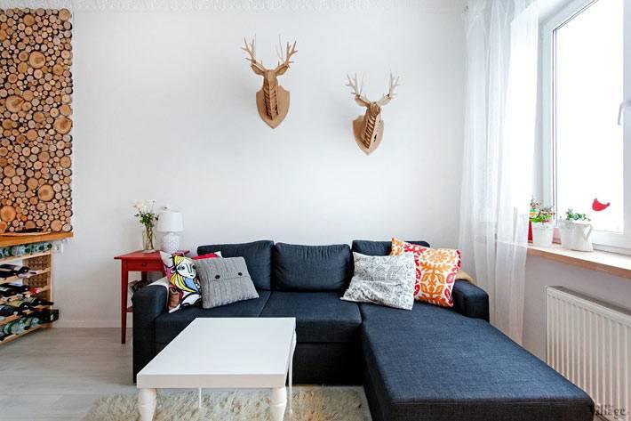 синий угловой диван возле окна в квартире