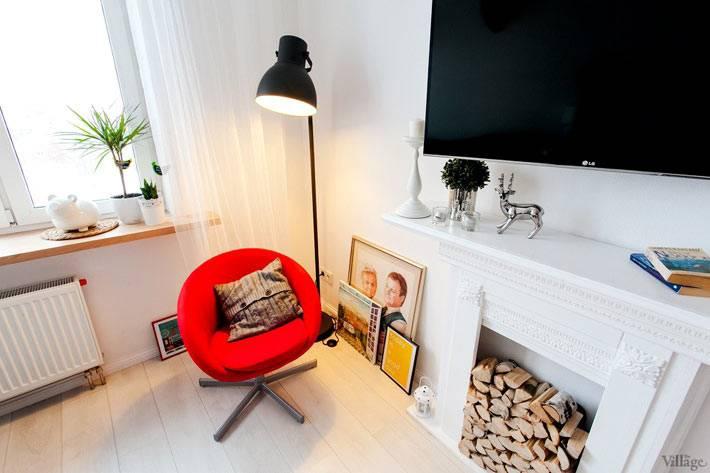 красное кресло и черный торшер в квартире с белыми стенами