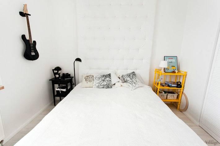 кровать с мягким белым изголовьем в интерьере спальни