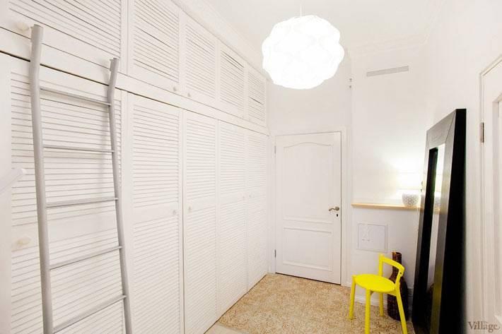 большой белый шкаф вдоль стены в спальне