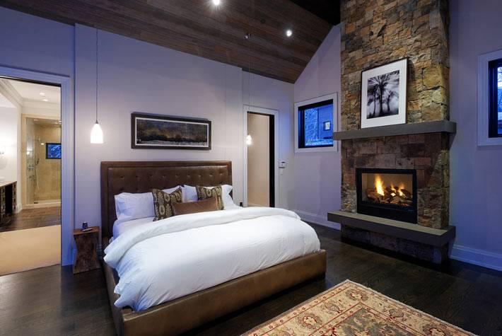 термокамин с каменной кладкой в интерьере спальни