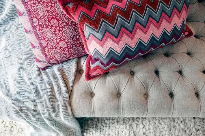 яркие декоративные подушки на прикроватном пуфе в спальне