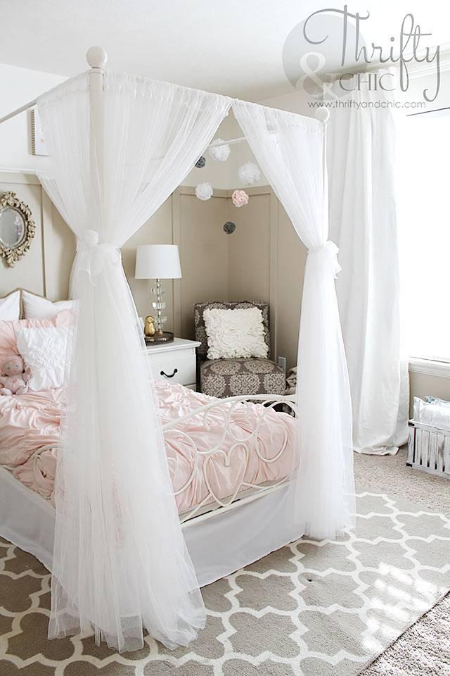 кровать с белым балдахином в детской спальне для девочки