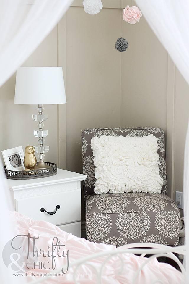 серое кресло возле белой прикроватной тумбочки