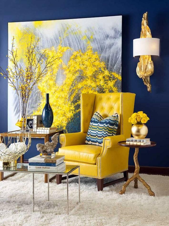 Ярко-желтые акценты на картине и кресле на фоне синей стены
