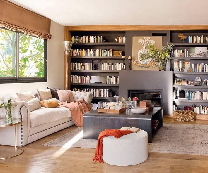 Уютная гостиная комната с книжными полками и камином