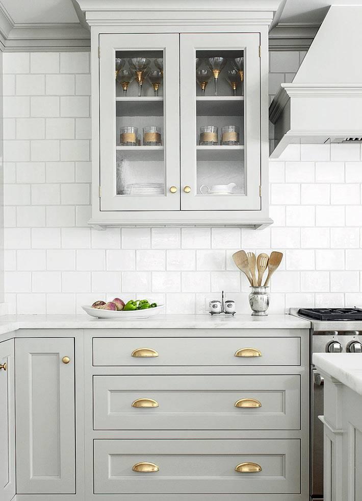 кухонная мебель серого цвета и золотой фурнитурой