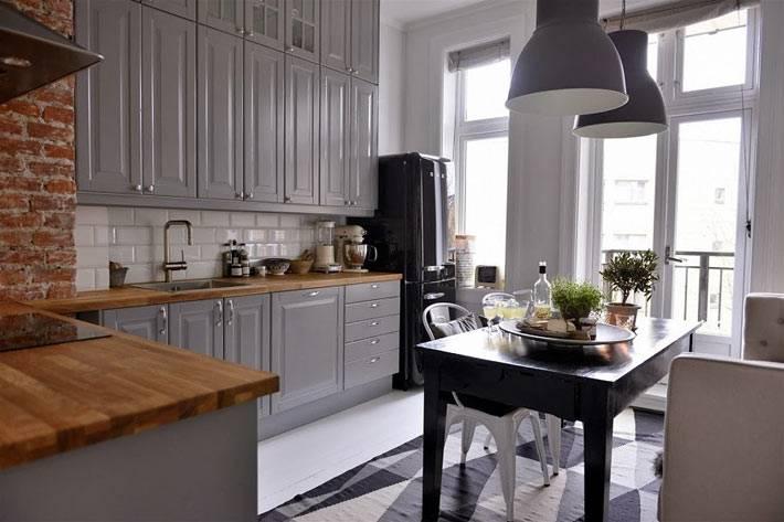 Интерьер кухни с кирпичной стеной и мебелью серого цвета