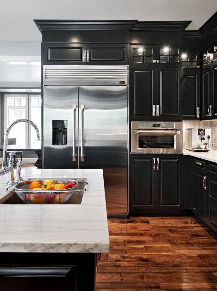 дизайн кухни с черным гарнитуром и паркетным полом